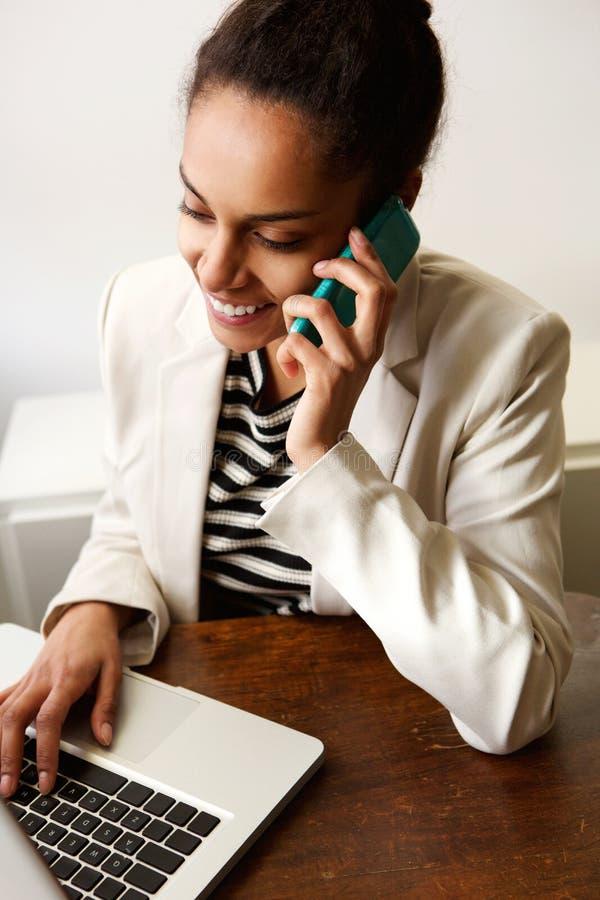 Jovem mulher que trabalha no escritório com telefone celular e portátil foto de stock royalty free