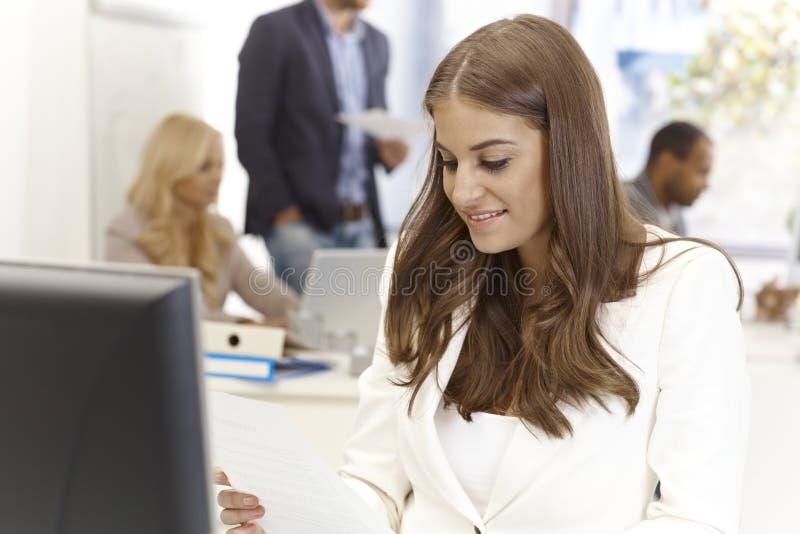 Jovem mulher que trabalha no escritório ocupado fotografia de stock royalty free