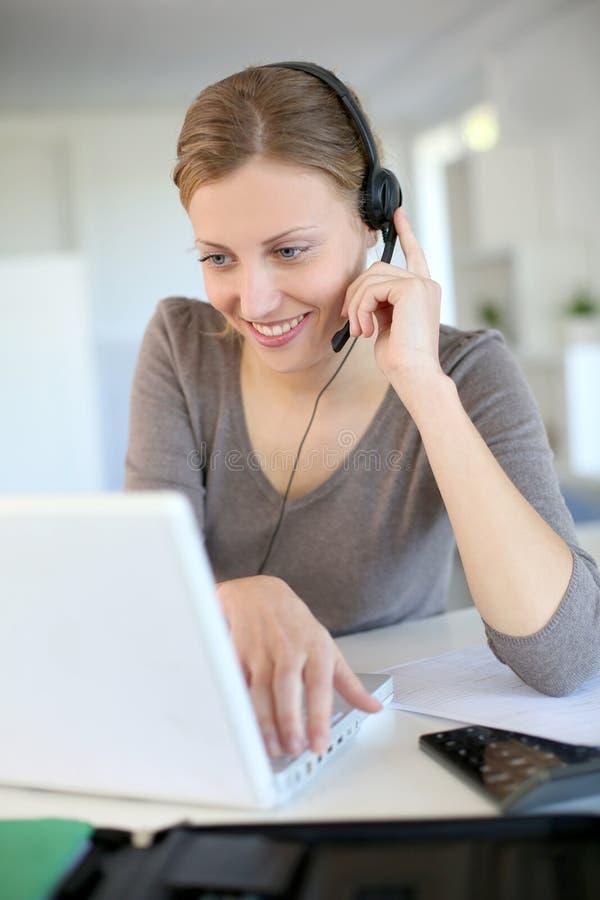 Jovem mulher que trabalha no portátil com auriculares fotografia de stock