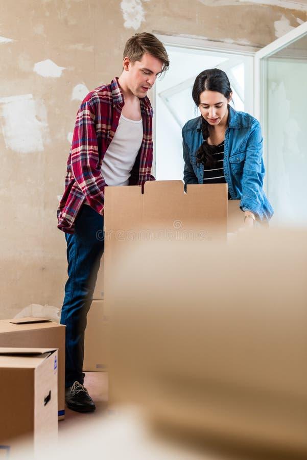 Jovem mulher que traz a caixa aberta que move-se dentro com seu noivo em fotos de stock
