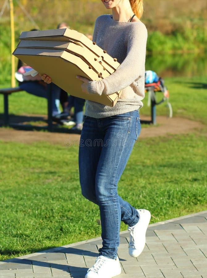 Jovem mulher que traz muitas caixas da pizza Piquenique no parque fotografia de stock royalty free