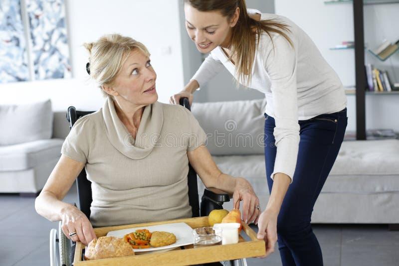 Jovem mulher que traz o almoço à mulher handicaped fotos de stock royalty free