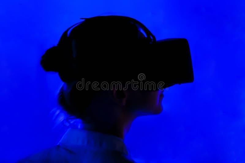 Jovem mulher que usa auriculares da realidade virtual na exposi??o interativa escura fotografia de stock