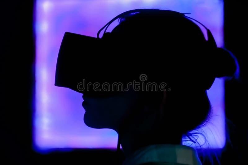 Jovem mulher que usa auriculares da realidade virtual na exposi??o interativa escura fotos de stock