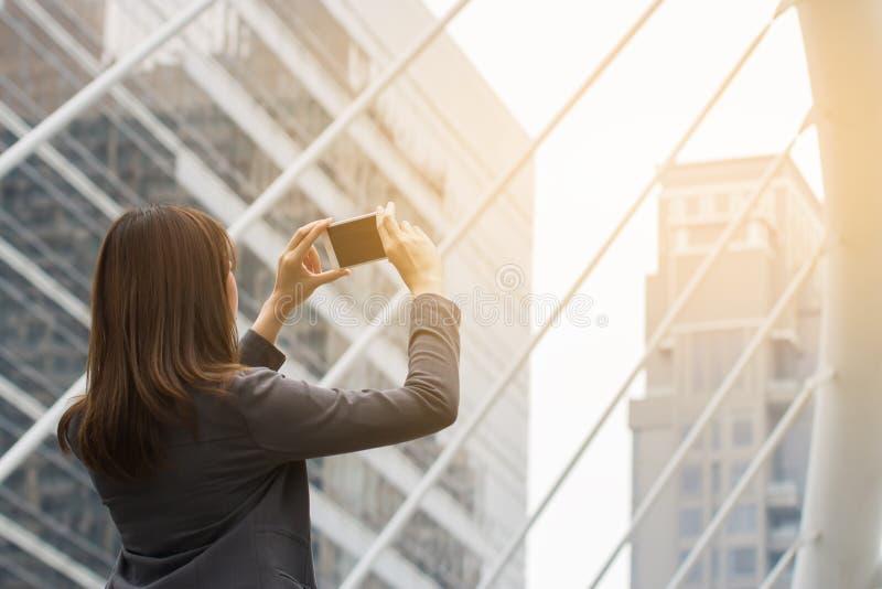 Jovem mulher que usa a câmera no telefone esperto fotografia de stock royalty free
