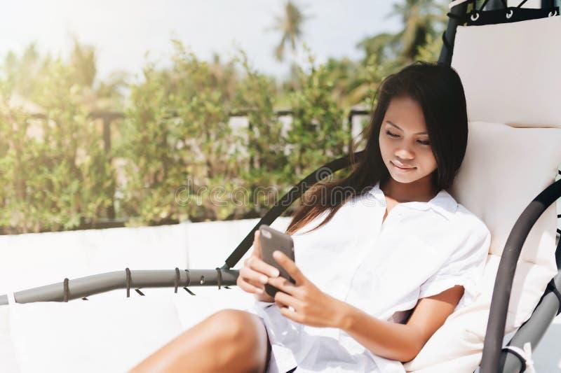 Jovem mulher que usa a conversa no telefone fora foto de stock royalty free
