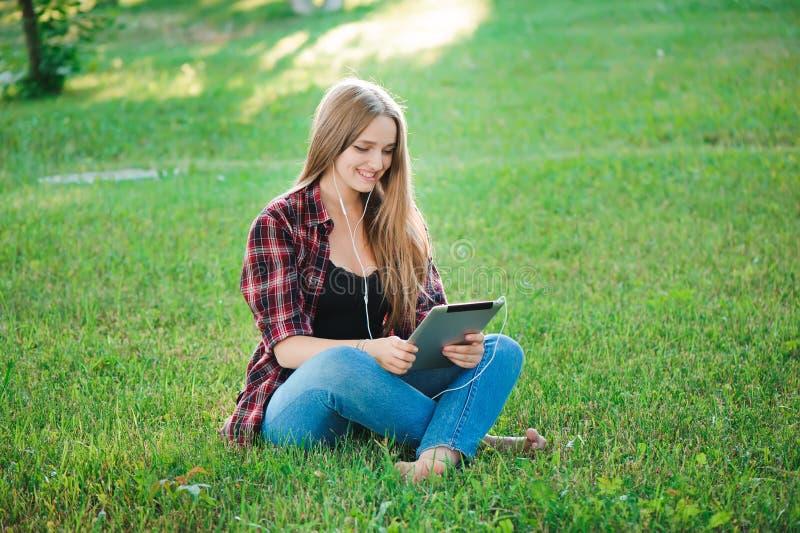 Jovem mulher que usa o assento exterior da tabuleta na grama, sorrindo foto de stock