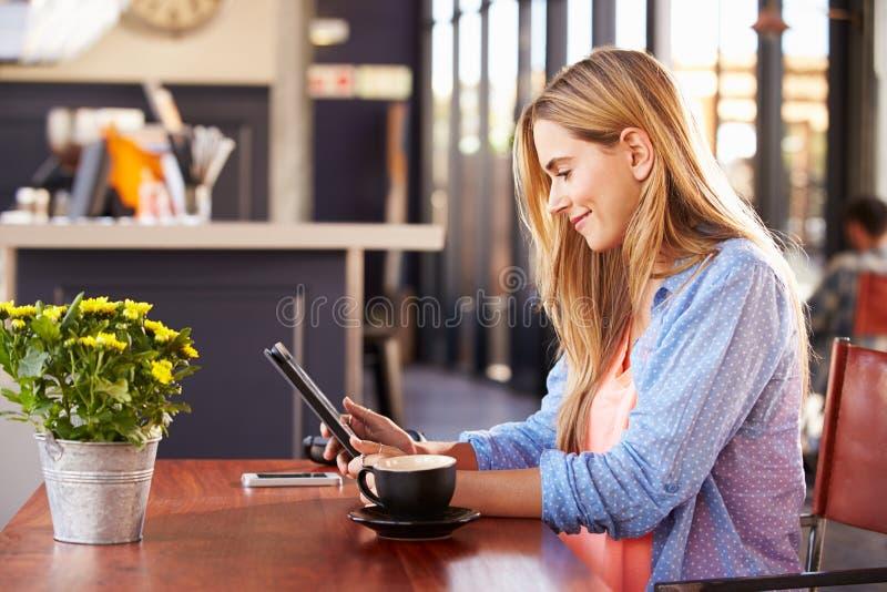 Jovem mulher que usa o computador em uma cafetaria imagem de stock