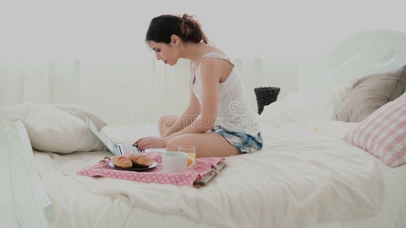 Jovem mulher que usa o portátil durante o café da manhã que senta-se na cama branca em casa Mensagem de datilografia da menina mo imagens de stock royalty free