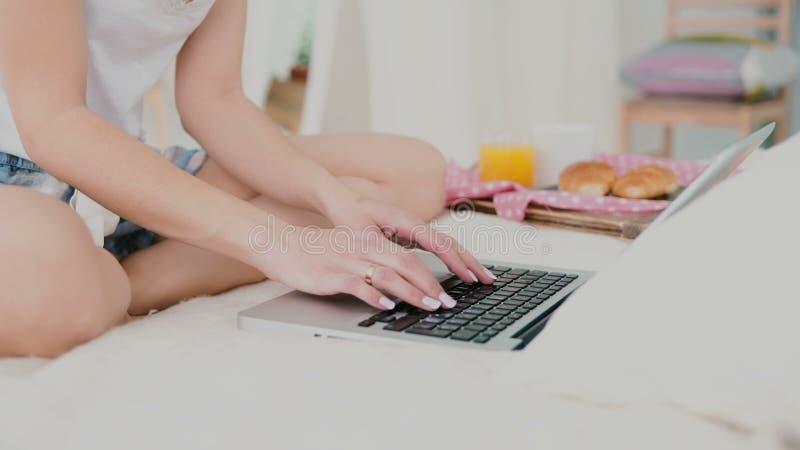 Jovem mulher que usa o portátil durante o café da manhã que senta-se na cama branca Opinião do close-up do suco de conversa e beb imagens de stock royalty free