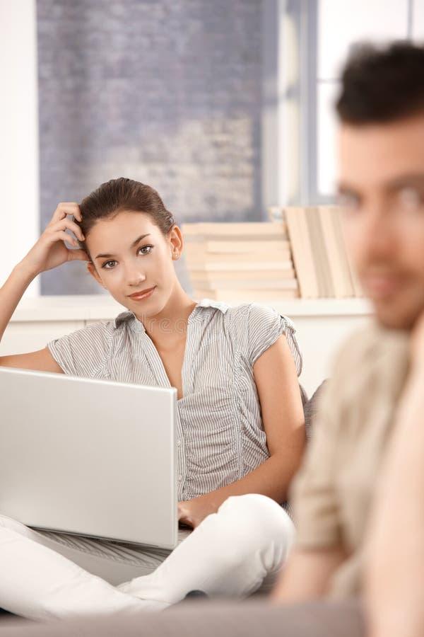 Jovem mulher que usa o portátil em casa que sorri foto de stock royalty free