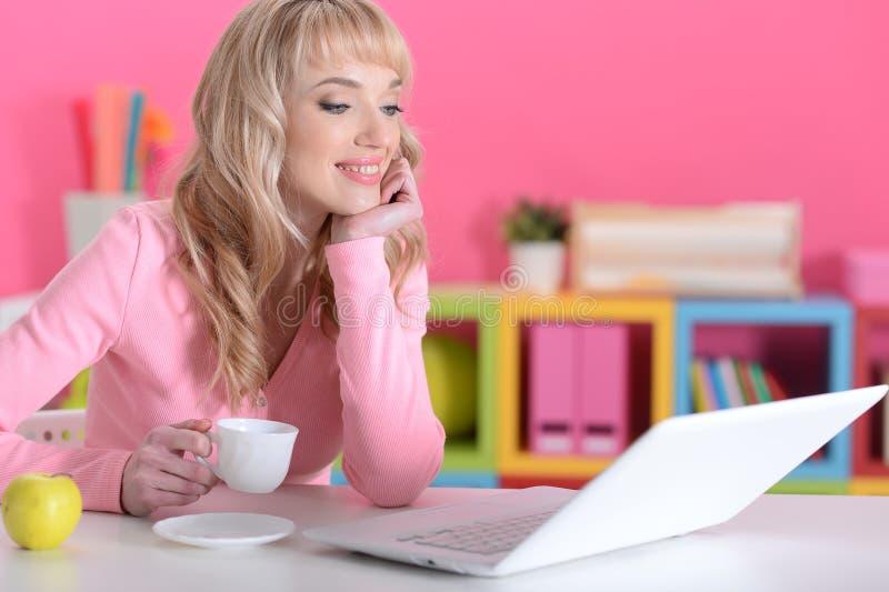 Jovem mulher que usa o portátil na mesa em casa fotografia de stock royalty free
