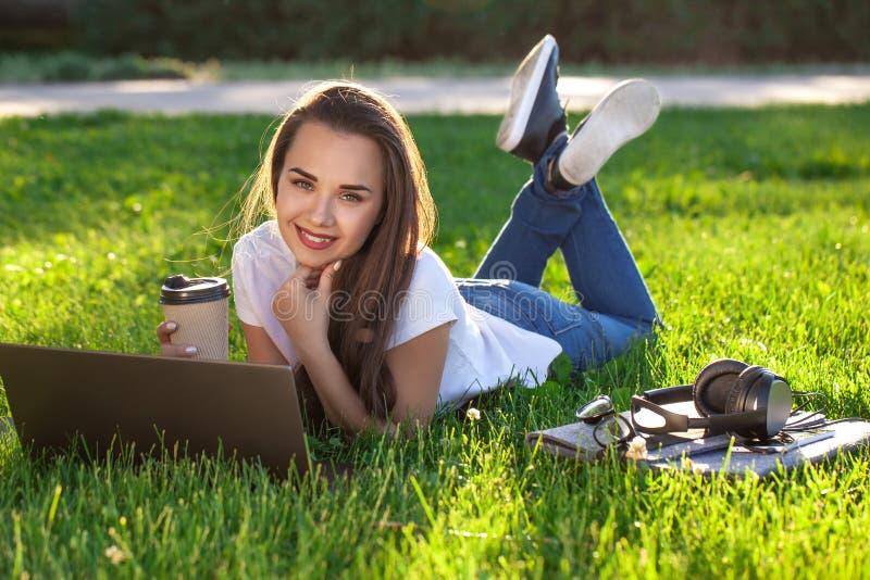 Jovem mulher que usa o portátil no parque que encontra-se na grama verde Conceito da atividade do tempo de lazer fotografia de stock
