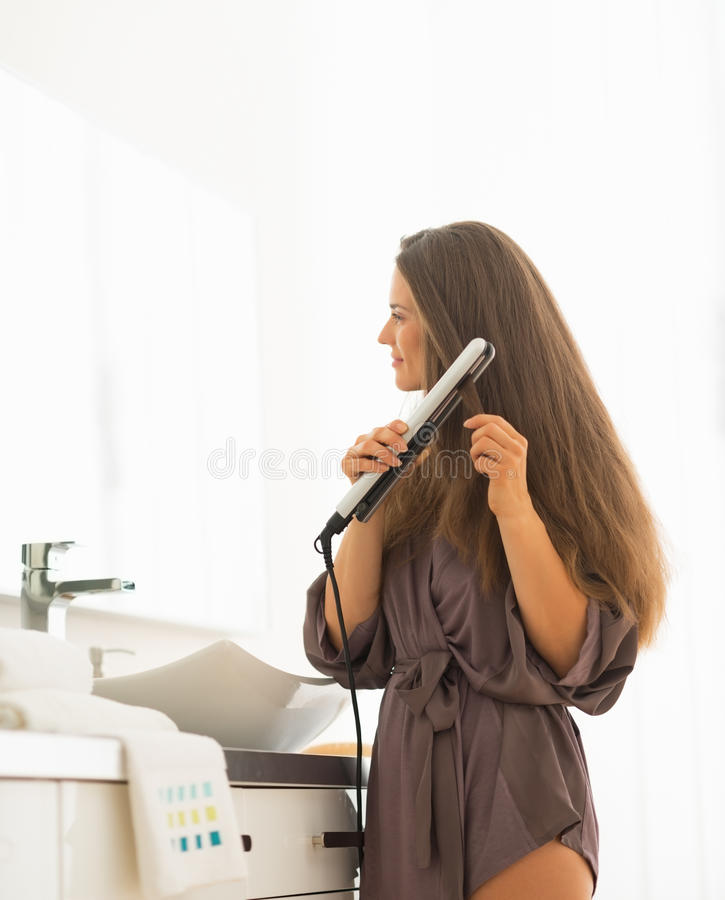 Jovem mulher que usa o straightener do cabelo no banheiro foto de stock