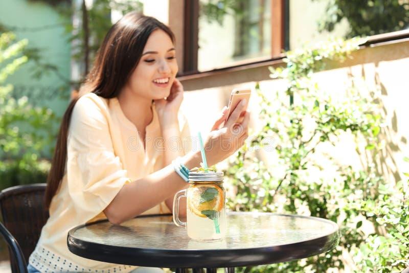 Jovem mulher que usa o telefone celular ao beber a limonada saboroso na tabela, fora fotos de stock royalty free