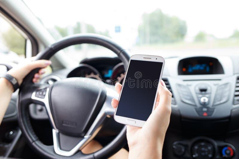 Jovem mulher que usa o telefone celular em um carro na estrada imagens de stock royalty free