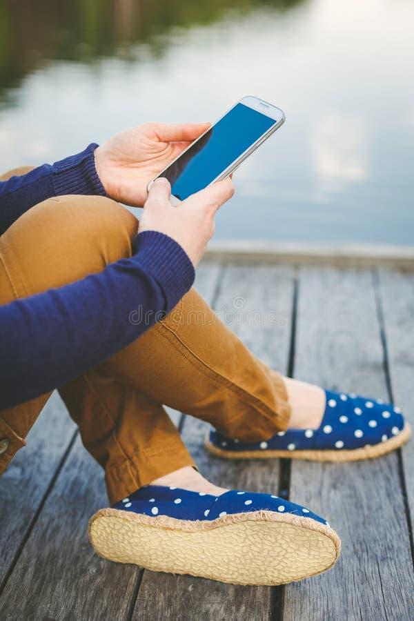 Jovem mulher que usa o telefone esperto foto de stock