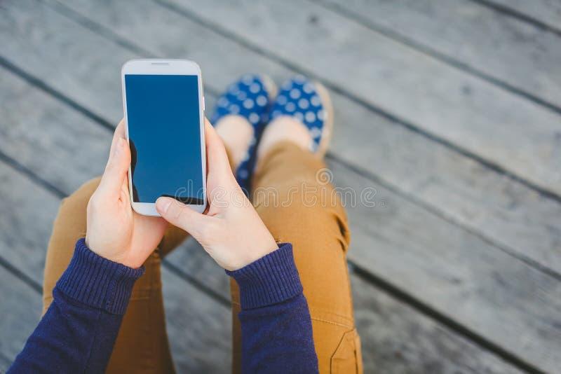 Jovem mulher que usa o telefone esperto imagens de stock