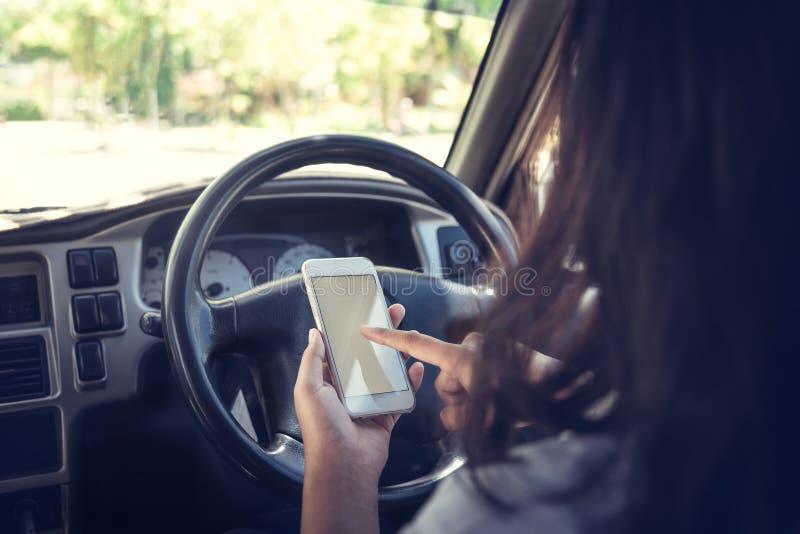 Jovem mulher que usa o telefone esperto ao conduzir um carro foto de stock