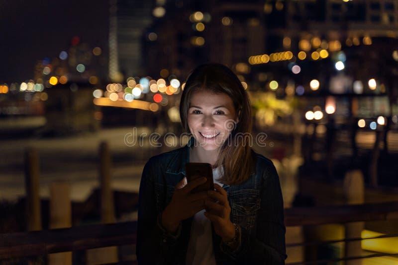 Jovem mulher que usa seu smartphone durante a noite luz da cidade como o fundo fotos de stock royalty free
