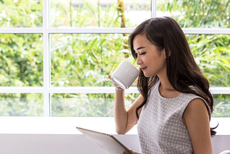 Jovem mulher que usa a tabuleta na cafetaria Telefone celular do uso da mulher na cafetaria imagens de stock