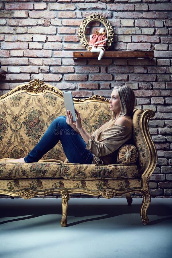 Jovem mulher que usa a tabuleta no interior barroco fotografia de stock royalty free