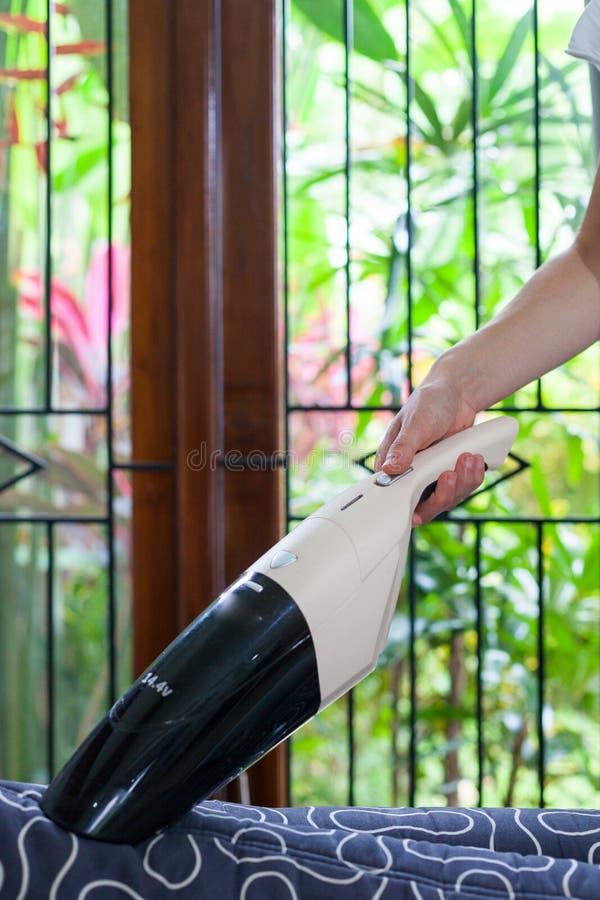 Jovem mulher que usa um aspirador de p30 manual pequeno ao limpar o estofamento de matéria têxtil no sofá fotografia de stock