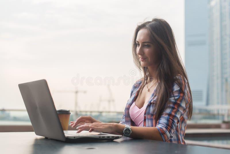 Jovem mulher que usa um portátil que trabalha fora Fêmea olhando a tela e datilografando no teclado fotos de stock