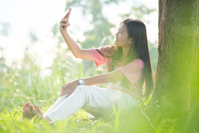 Jovem mulher que usa um smartphone no parque, retrato de um selfie bonito da jovem mulher no parque com um smartphone fotos de stock royalty free