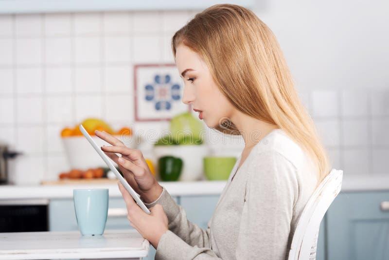 Jovem mulher que usa um tablet pc em casa imagens de stock