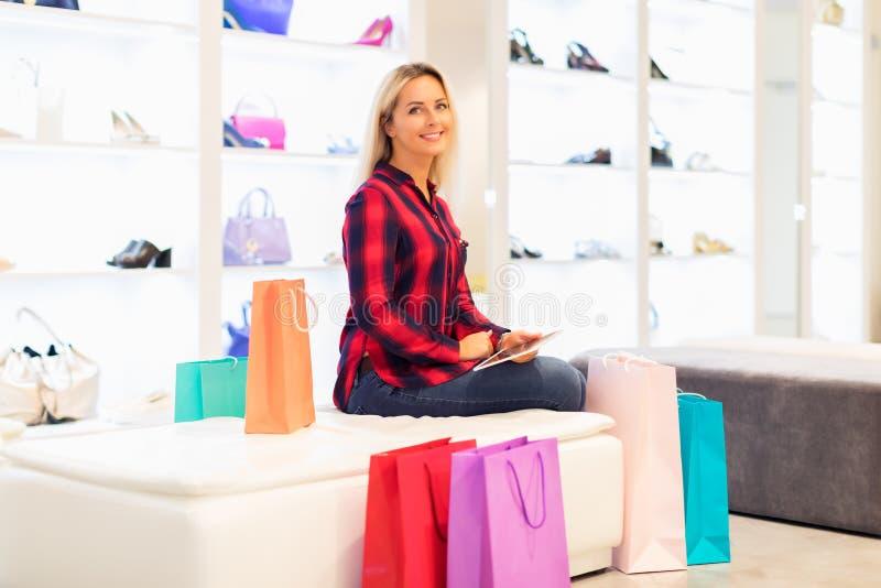 Jovem mulher que usa um tablet pc na loja da forma fotografia de stock