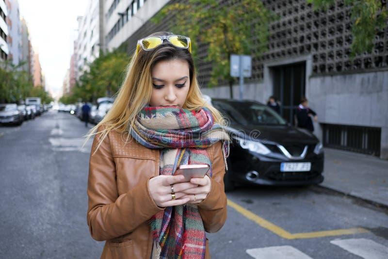 Jovem mulher que usa um telefone esperto na rua fotos de stock royalty free