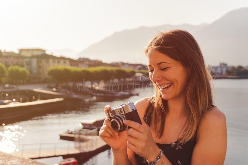 Jovem mulher que usa uma câmera do vintage na frente do passeio do lago em Ascona imagens de stock royalty free