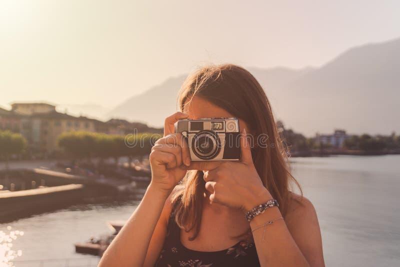 Jovem mulher que usa uma c?mera do vintage na frente do passeio do lago em Ascona foto de stock royalty free