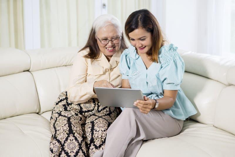 Jovem mulher que usa uma tabuleta com sua mãe foto de stock royalty free