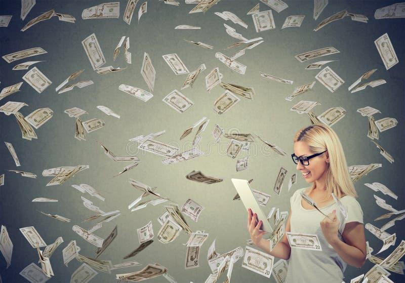Jovem mulher que usa uma tabuleta que constrói o dinheiro em linha do salário de negócio sob o dinheiro que cai para baixo foto de stock royalty free