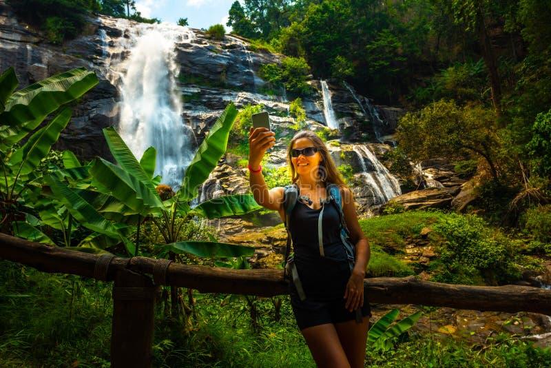 A jovem mulher que veste óculos de sol toma o selfie em seu smartphone com a cachoeira de Wachirathan no fundo Doi Inthanon nacio imagens de stock royalty free