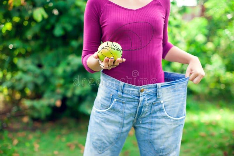 Jovem mulher que veste calças de brim fracas grandes com peso da maçã à disposição - fotografia de stock