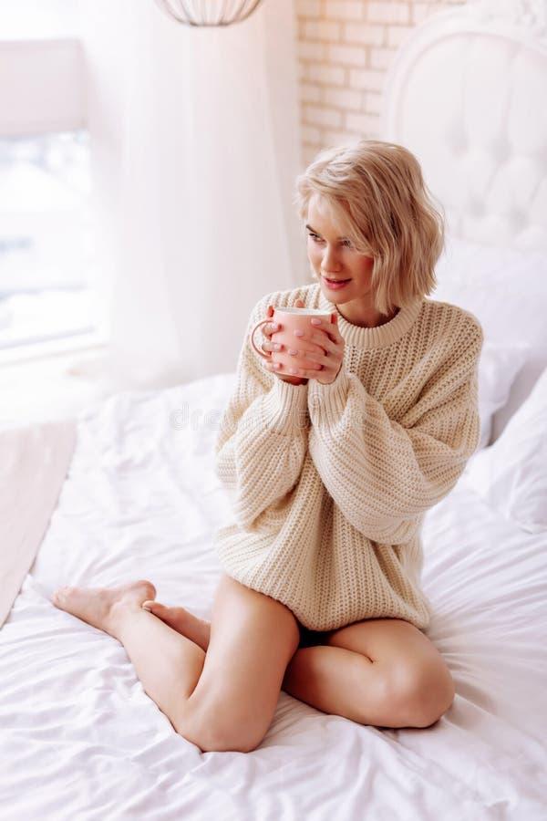 Jovem mulher que veste o copo bege da terra arrendada da camiseta com chá quente fotografia de stock royalty free