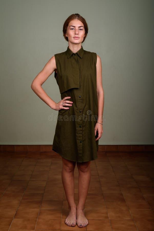 Jovem mulher que veste o vestido sem mangas verde contra o backg colorido fotografia de stock