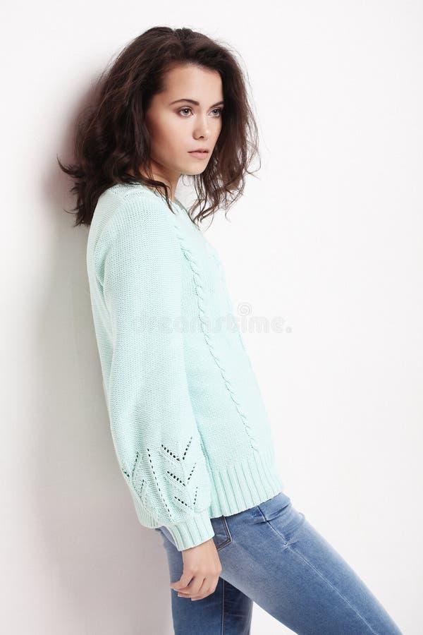 Jovem mulher que veste a roupa ocasional, levantando no fundo branco fotografia de stock