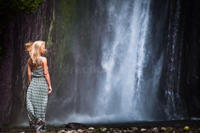 Jovem mulher que viaja à cachoeira foto de stock