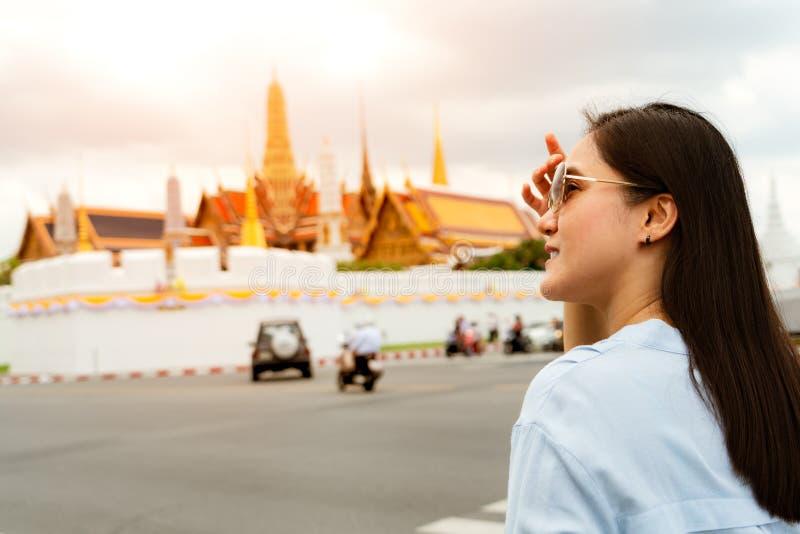 Jovem mulher que viaja ao palácio e a Wat Phra Keaw grandes no por do sol em Banguecoque, Tailândia imagens de stock royalty free