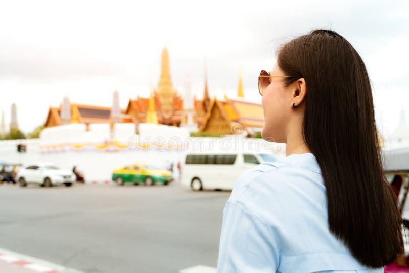 Jovem mulher que viaja ao palácio e a Wat Phra Keaw grandes no por do sol em Banguecoque, Tailândia fotografia de stock