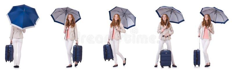 Jovem mulher que viaja com a mala de viagem e o guarda-chuva isolados no wh fotos de stock