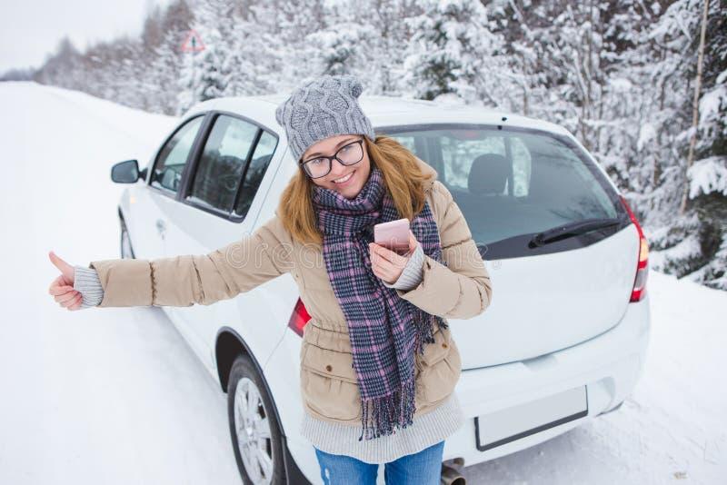 Jovem mulher que viaja na estrada coberto de neve do inverno fotos de stock