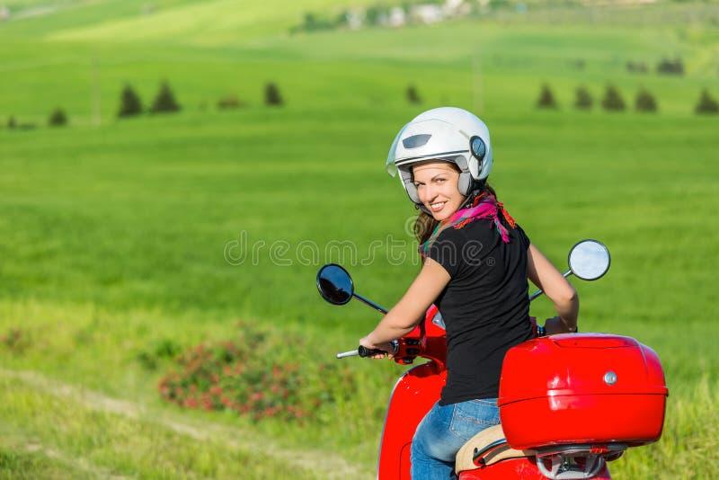 Jovem mulher que viaja por um 'trotinette' fotografia de stock