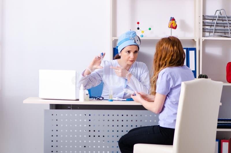 Jovem mulher que visita o otolaryngologist f?mea do doutor foto de stock