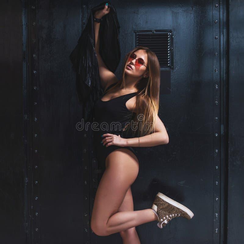 Jovem mulher quente com o corpo perfeito do ajuste que levanta no roupa de banho e nos óculos de sol que mantêm um revestimento c imagens de stock royalty free