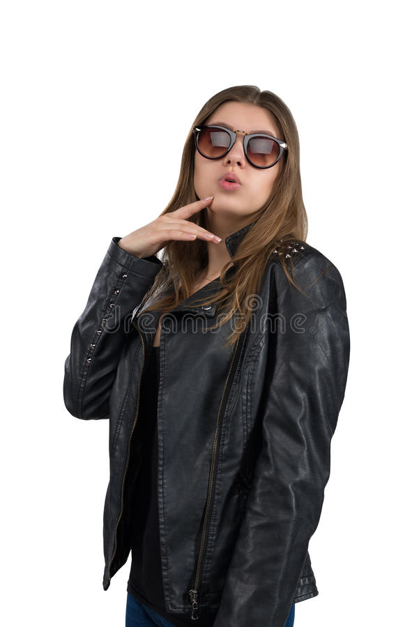 Jovem mulher quente glamoroso em um casaco de cabedal e em uns óculos de sol marrons, isolados no fundo branco Rua, forma da roch foto de stock